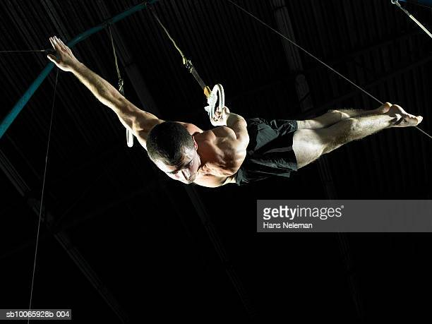 Male gymnast (16-17) balancing on ring, low angle view