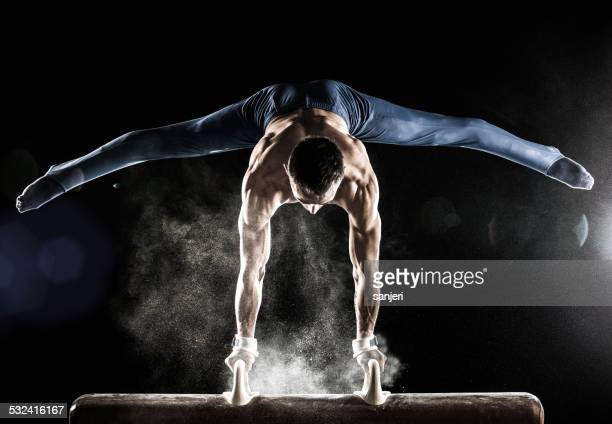 male gymnast doing handstand on pommel horse - gymnastics stock pictures, royalty-free photos & images