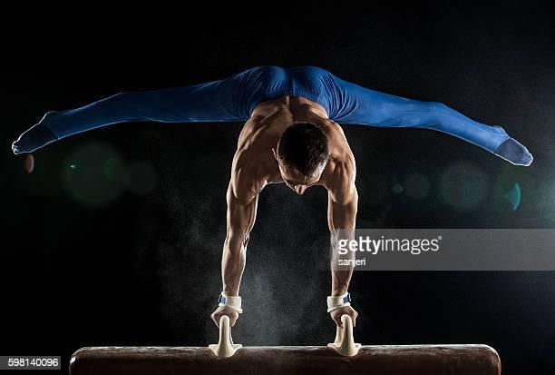 Männliche Sportgymnastin macht handstand auf Seitpferd