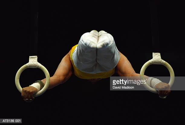Male gymnast in horizontal holding position on rings, rear view