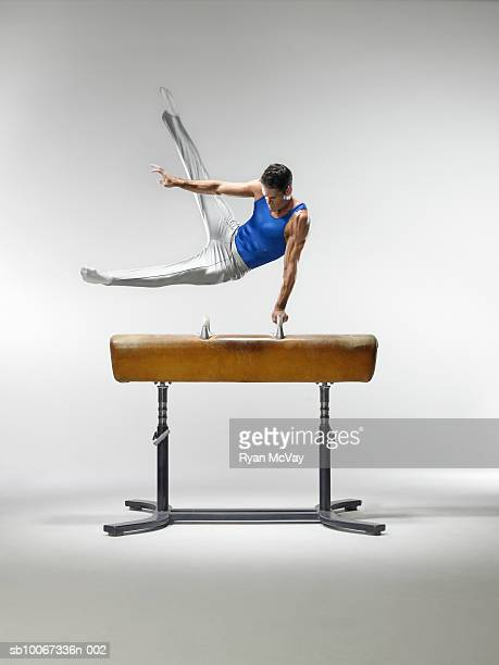 Male gymnast on pommel horse, studio shot