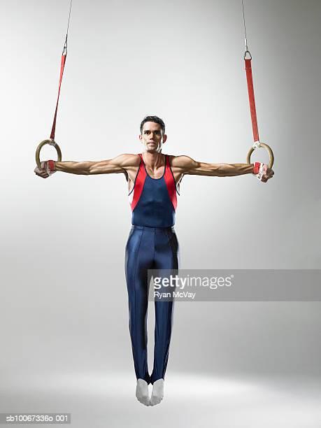 Male gymnast on rings, studio shot