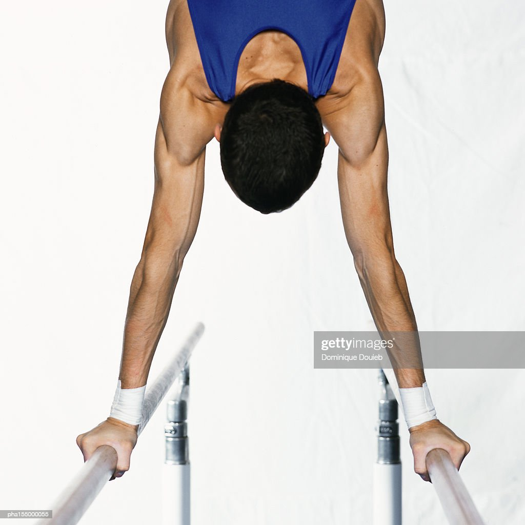 Male gymnast performing handstand on parallel bars, upper section, rear view. : ストックフォト