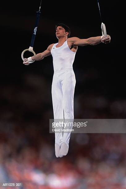 Male gymnast performing iron cross on rings