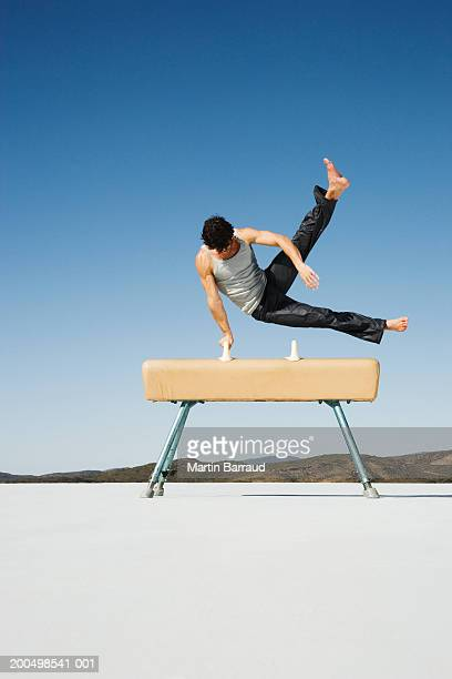 Male gymnast performing on pommel horse, outdoors