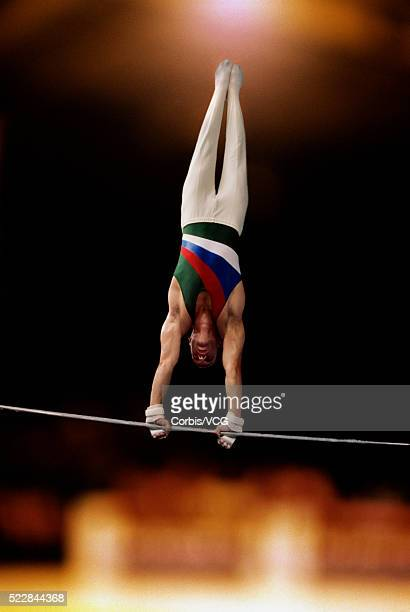 male gymnast performing on the high bar - horizontal bars stock pictures, royalty-free photos & images