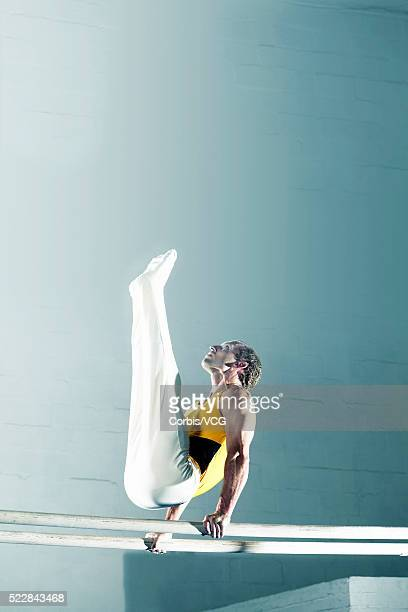 male gymnast performing on the parallel bars - parallel bars gymnastics equipment stock photos and pictures
