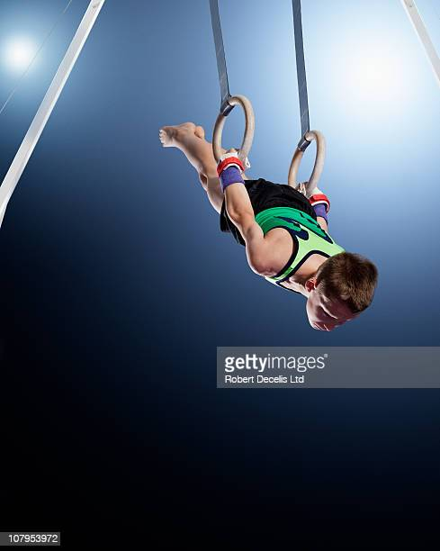 male gymnast performing routine on rings - gymnastics stock pictures, royalty-free photos & images