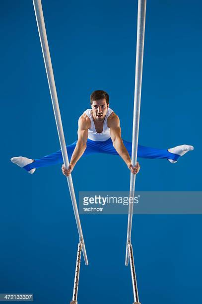 Male gymnast performing routine on the parallel bars
