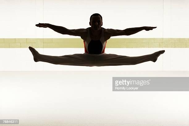 Male gymnast performing splits in floor exercise