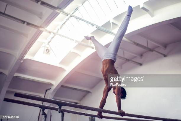 male gymnast practicing on parallel bars - artistic gymnastics stock pictures, royalty-free photos & images