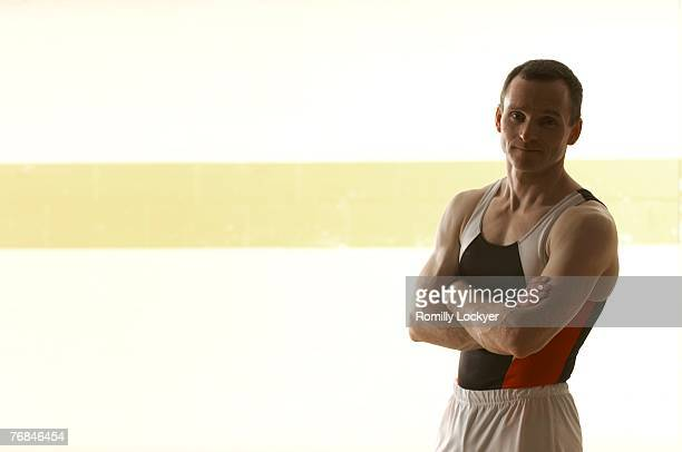 male gymnast standing in gymnasium, arms crossed, portrait - gymnastics poses stock pictures, royalty-free photos & images