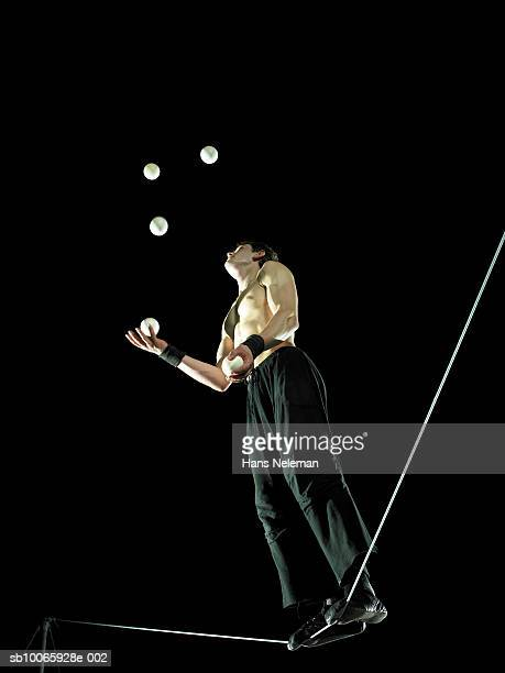 Male gymnast standing on tightrope, juggling balls, low angle view