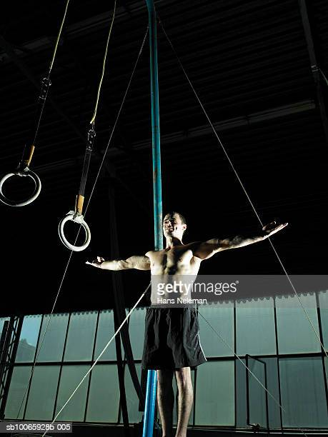 Male gymnast (16-17) standing with arms out in front of ring, low angle view