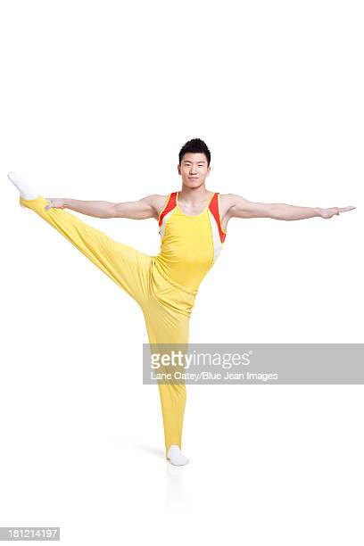 Male gymnastic athlete standing on one leg
