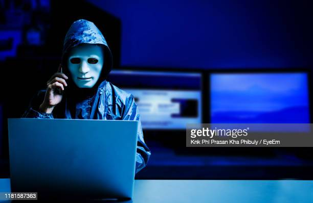 male hacker wearing mask while using laptop at table in darkroom - violation d'accès informatique photos et images de collection