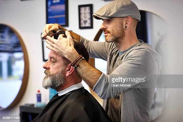 Male hairstylist cutting client's hair