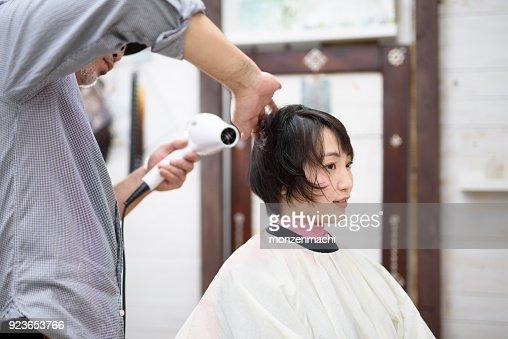 Male hairstylist drying hair of customer in hair salon