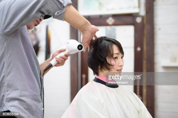 Male hairstylist drying hair of customer in hair salon