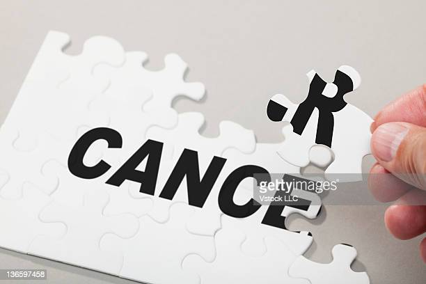 Male hand arranging Puzzle Pieces spelling out CANCER