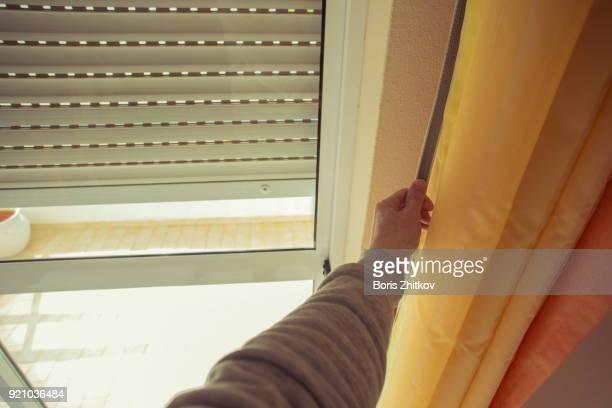 male hand closing rolling shutter - fensterladen stock-fotos und bilder