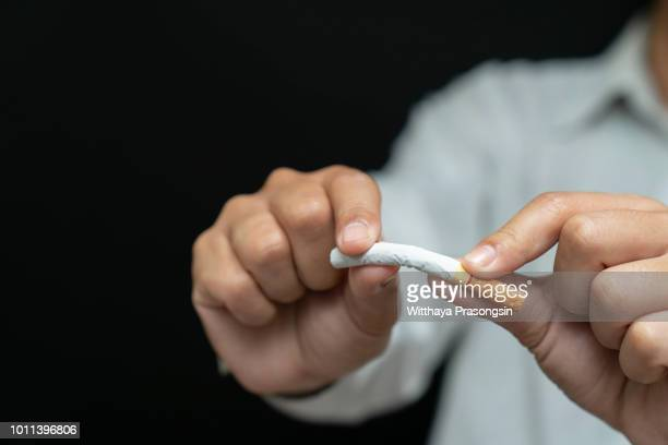 male hand crushing cigarette