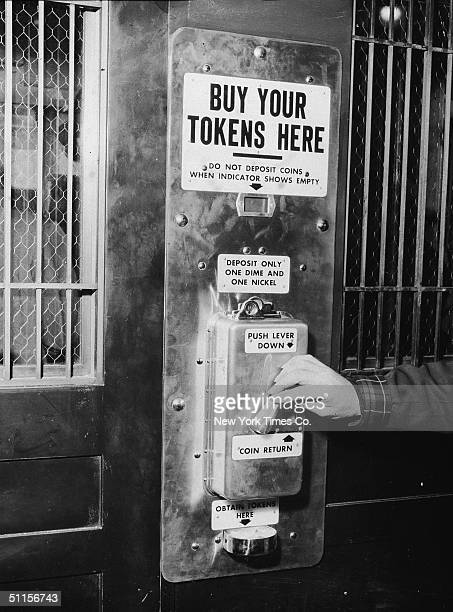 A male hand depresses a lever on the first subway token vending machine at Change Booth 504 at Sixth Avenue and 40th Street in New York April 19 1954...