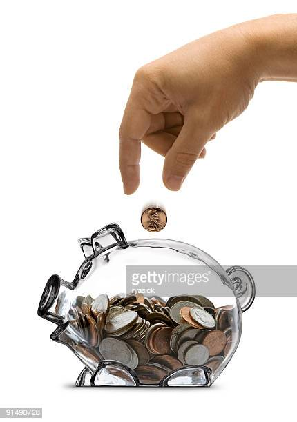Male Hand Dropping Coin Into Half Filled Piggy Bank Isolated