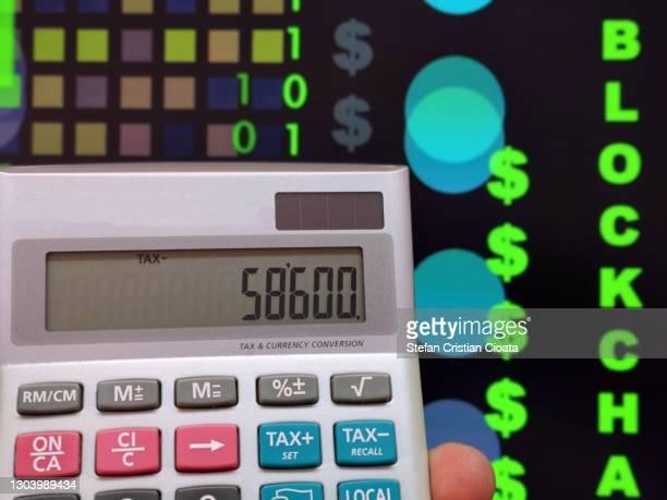 male hand holding a calculator. financial technology concept. crypto and block chain. - cristian neri foto e immagini stock