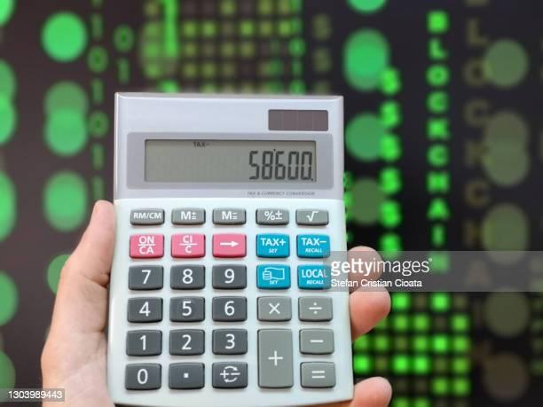 male hand holding a calculator. financial technology concept. crypto and block chain digital background. - cristian neri foto e immagini stock
