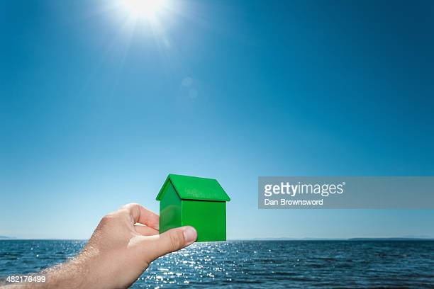 Male hand holding a green toy house aligned with sea horizon