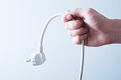 Male Hand Holding A Power Cable - Saving Energy Concept