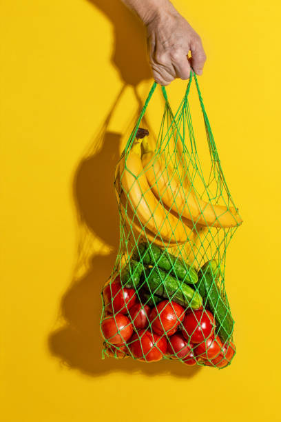 Male hand holding a white mesh bag with vegetables on yellow