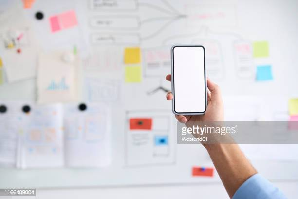 male hand holding aloft a smartphone in front of a whiteboard - holding aloft stock pictures, royalty-free photos & images