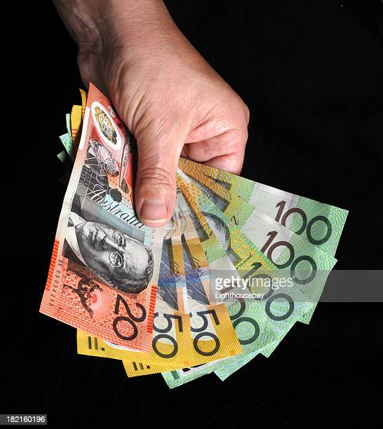 Male hand holding Australian currency in notes