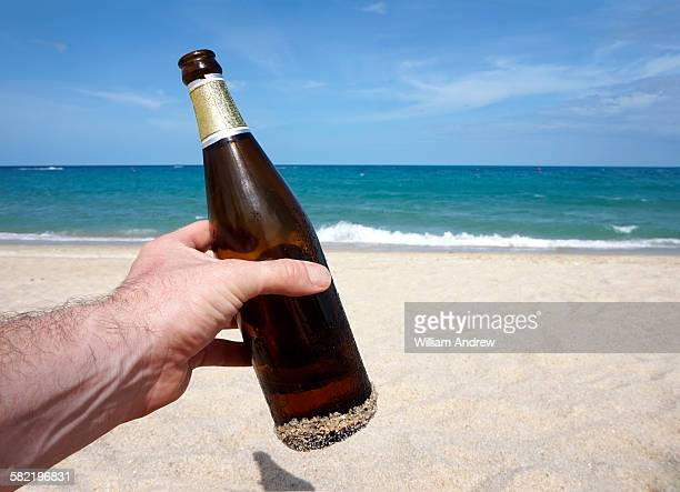 Male hand holding beer bottle on beach