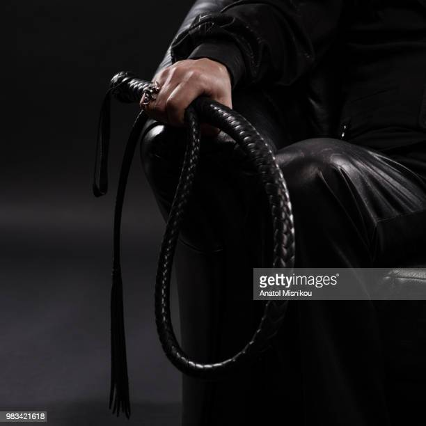 male hand holding black leather whip - men being spanked stock pictures, royalty-free photos & images