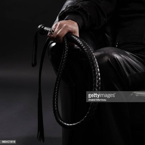 male hand holding black leather whip - peitsche stock-fotos und bilder