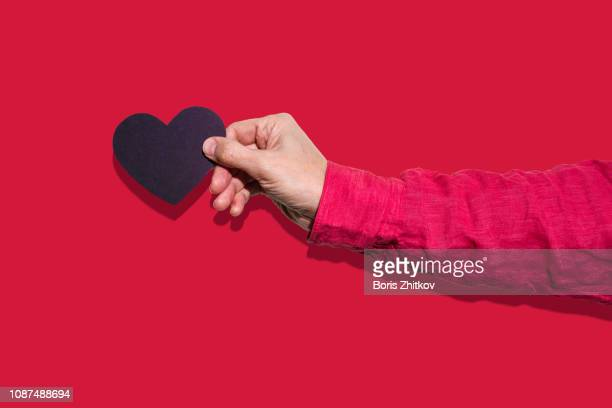 male hand holding black paper heart - long sleeved stock pictures, royalty-free photos & images