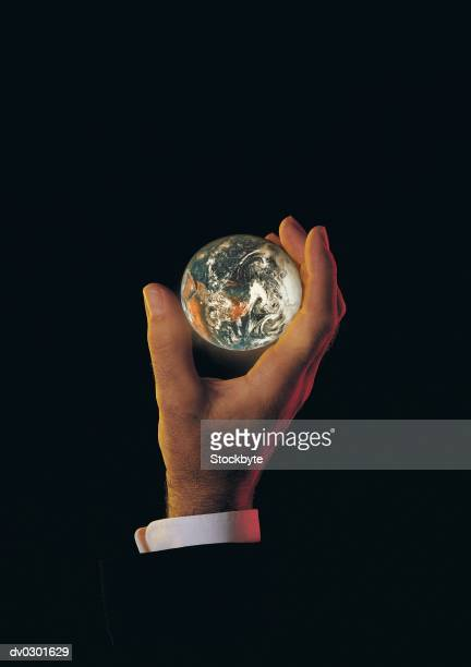 male hand holding earth or globe - world at your fingertips stock pictures, royalty-free photos & images