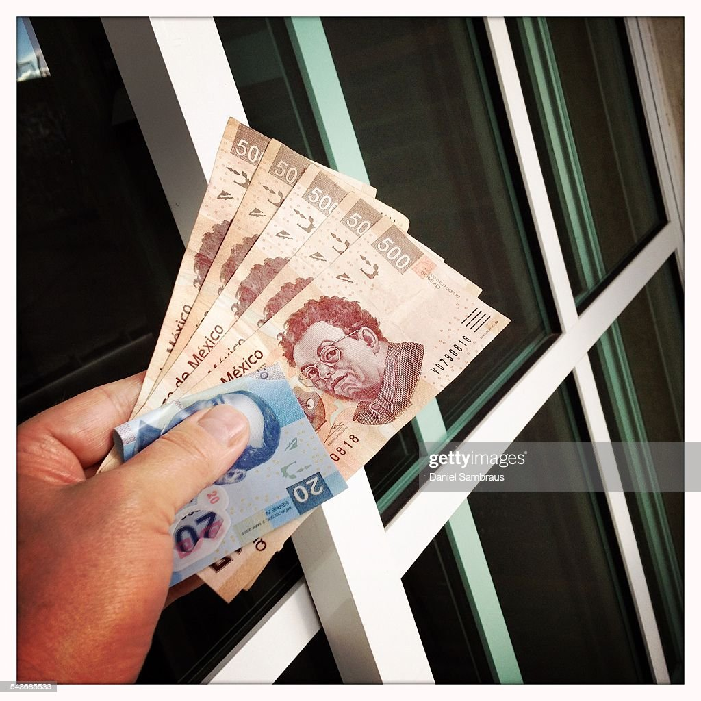 A male hand holding Mexican pesos notes. The 500 peso note has the image of Diego Riviera.
