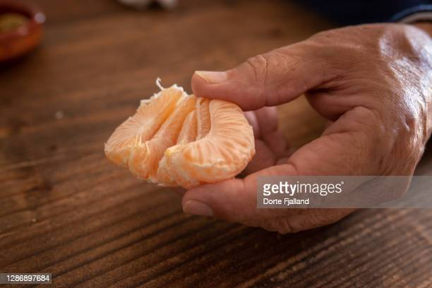 male hand holding some slices of a mandarin - dorte fjalland ストックフォトと画像