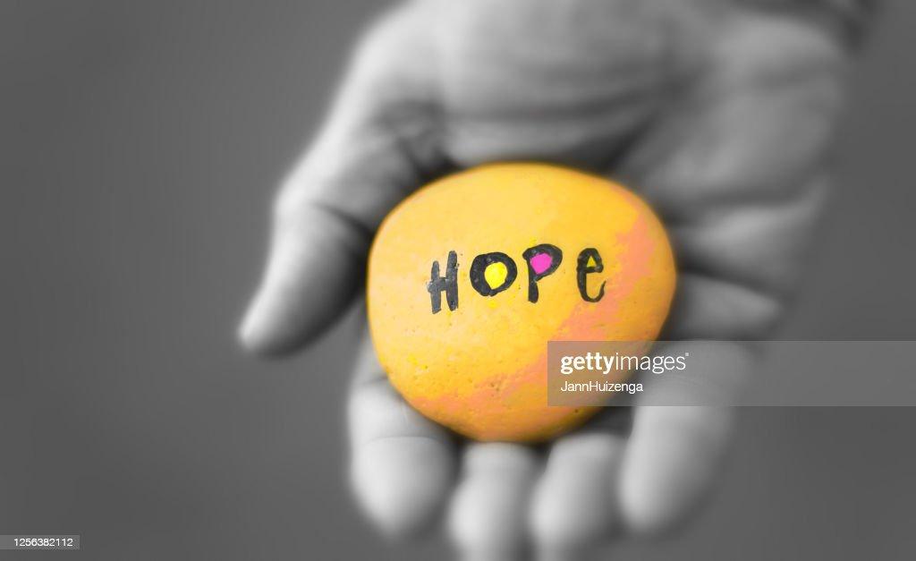 "Male Hand Holding Yellow Stone Reading ""HOPE"" : Stock Photo"