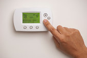 Male hand on digital thermostat set at 78 degrees