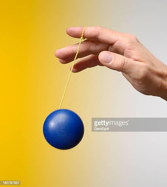 Mâle main jouant avec un blu yo-yo sur fond jaune