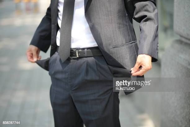 Male hand pulling pocket out of pants to show it is empty