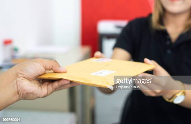 male hand send mail envelope to the female of post office before sending - send stock pictures, royalty-free photos & images