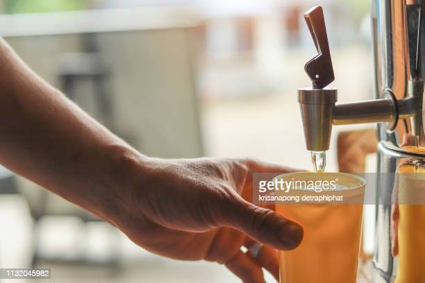 male hand serving water of a water cooler in plastic cup. - water cooler stock pictures, royalty-free photos & images