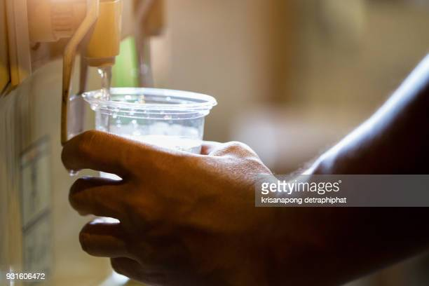 Male hand serving water of a water cooler in plastic cup.