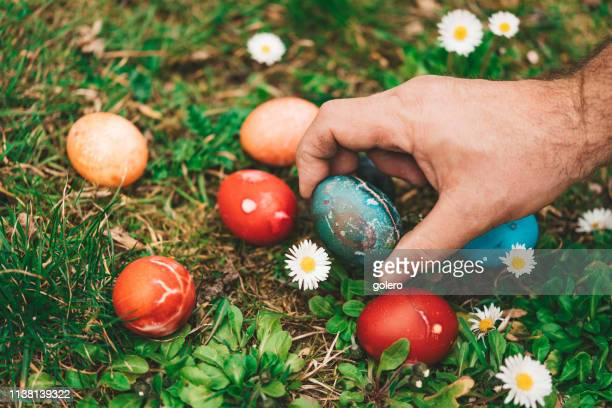 male hand taking colorful easter egg - easter religious background stock pictures, royalty-free photos & images